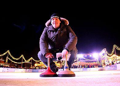 Eismeister kniet auf dem Eis, davor zwei Eisstöcke
