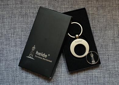 Silberner, runder Schlüsselanhänger mit dem Schriftzug Heide inklusive Einkaufschip 6,90€