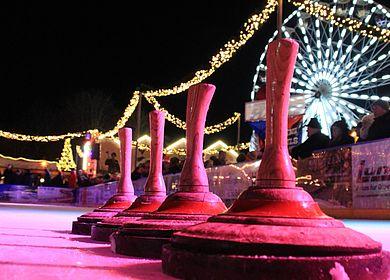 vier Eisstöcke hintereinander im Hintergrund das beleuchtete Riesenrad